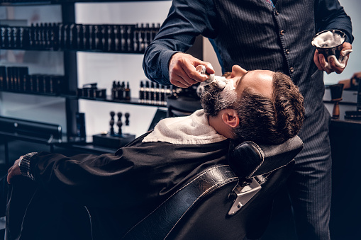 Barber applies shaving foam to a man's face in a saloon.
